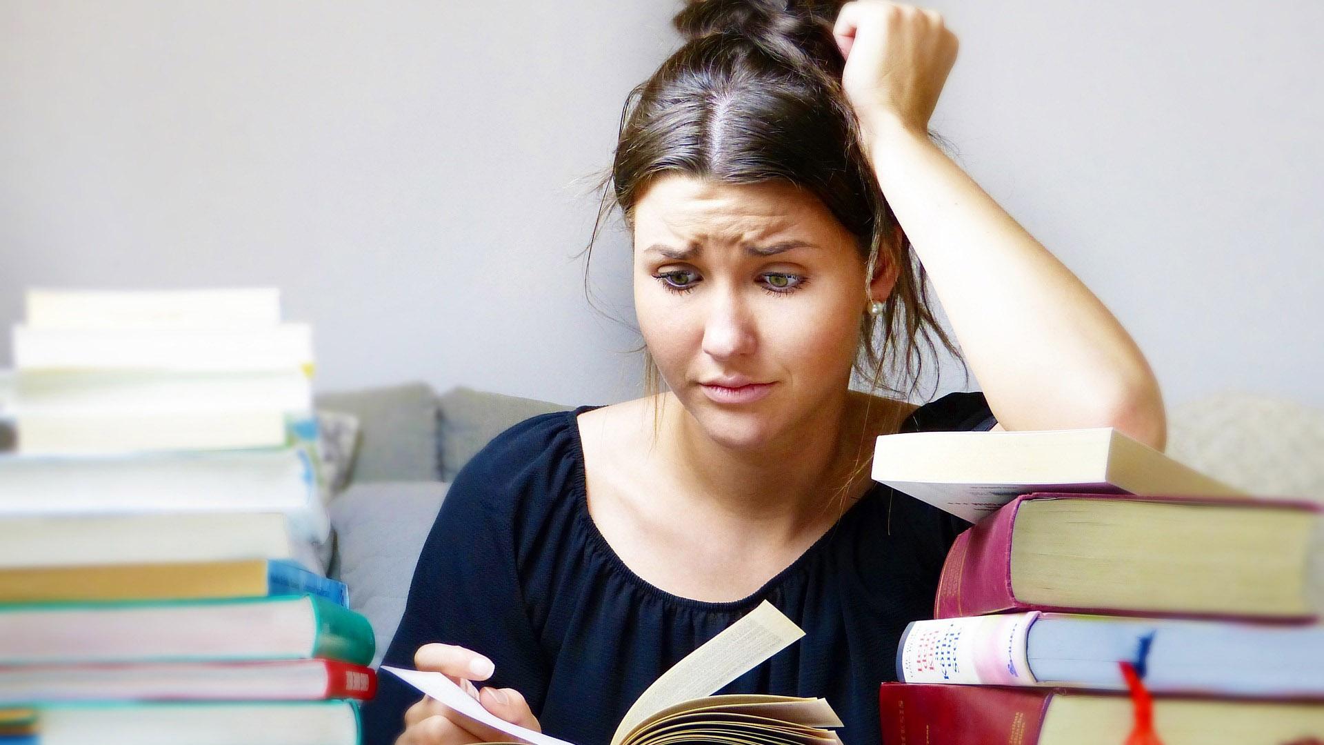 Joven estudiando alrededor de muchos libros
