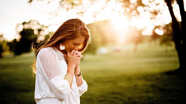 Joven rezando en un jardin