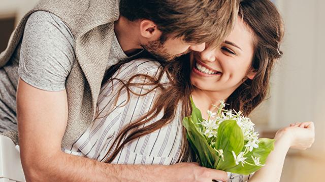 joven pareja abrazándose con ramo de flores