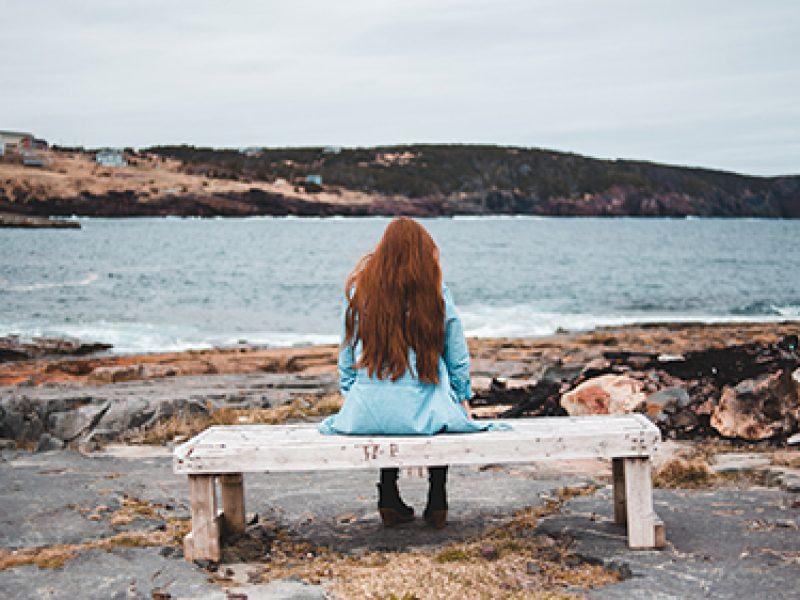 joven a solas observando el mar