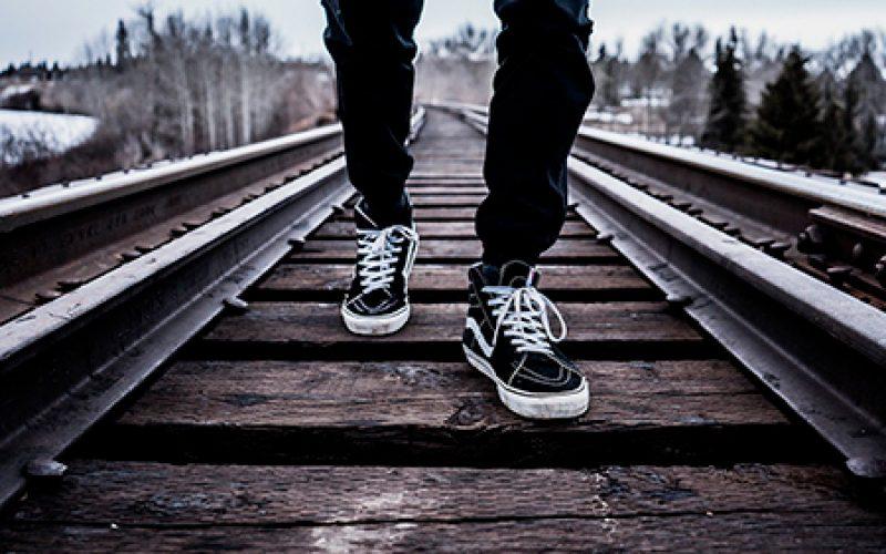 joven caminando por los rieles del tren