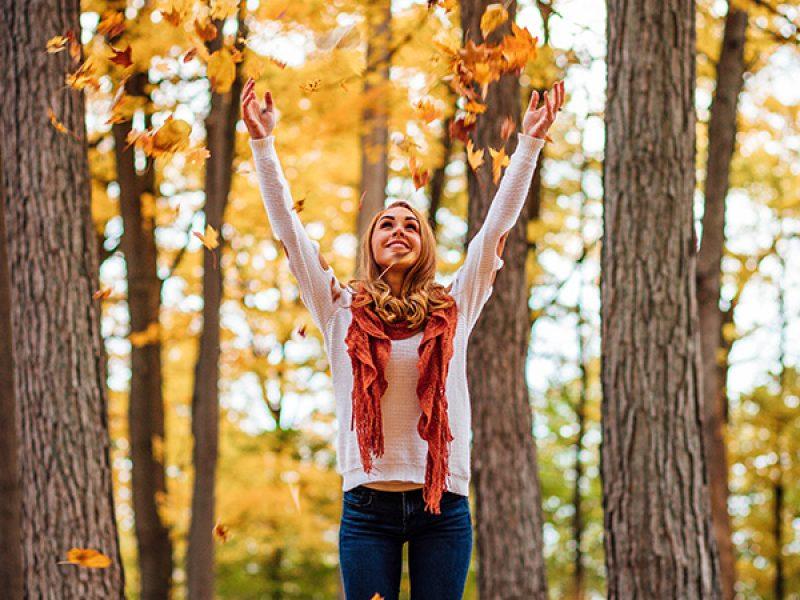 joven jugando con las hojas de otoño