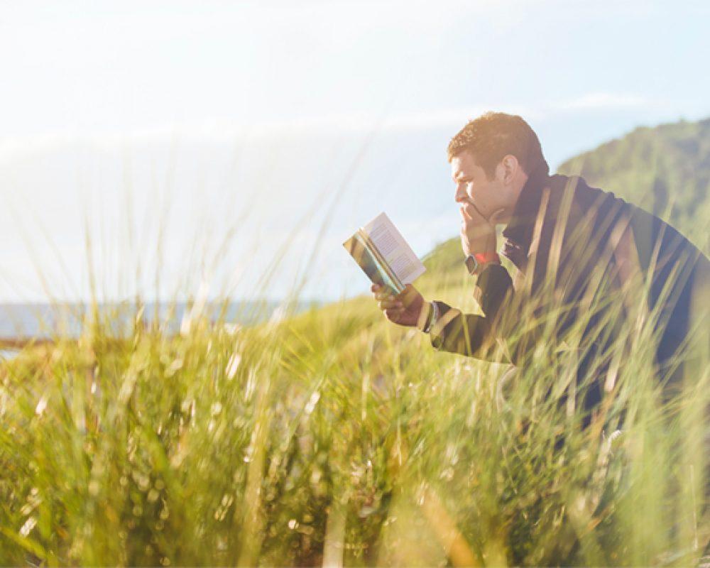 joven leyendo en medio de la naturaleza