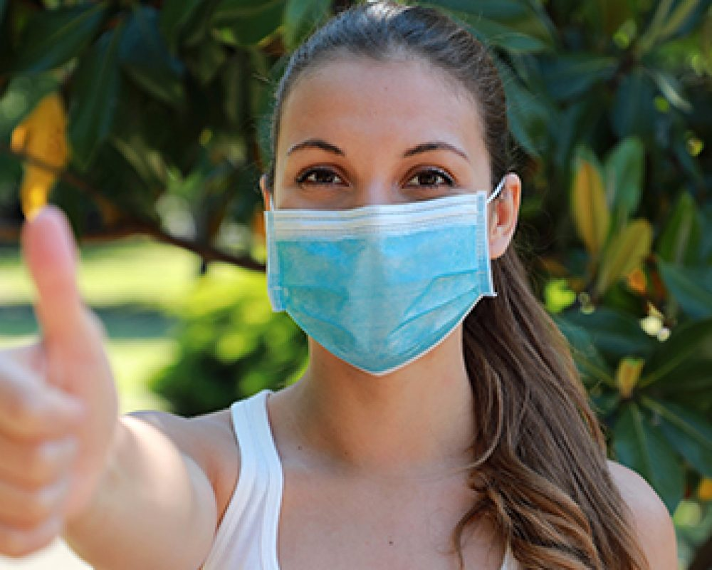 COVID-19 Optimistic sporty girl wearing surgical mask on face during pandemic coronavirus disease showing thumbs up in city park